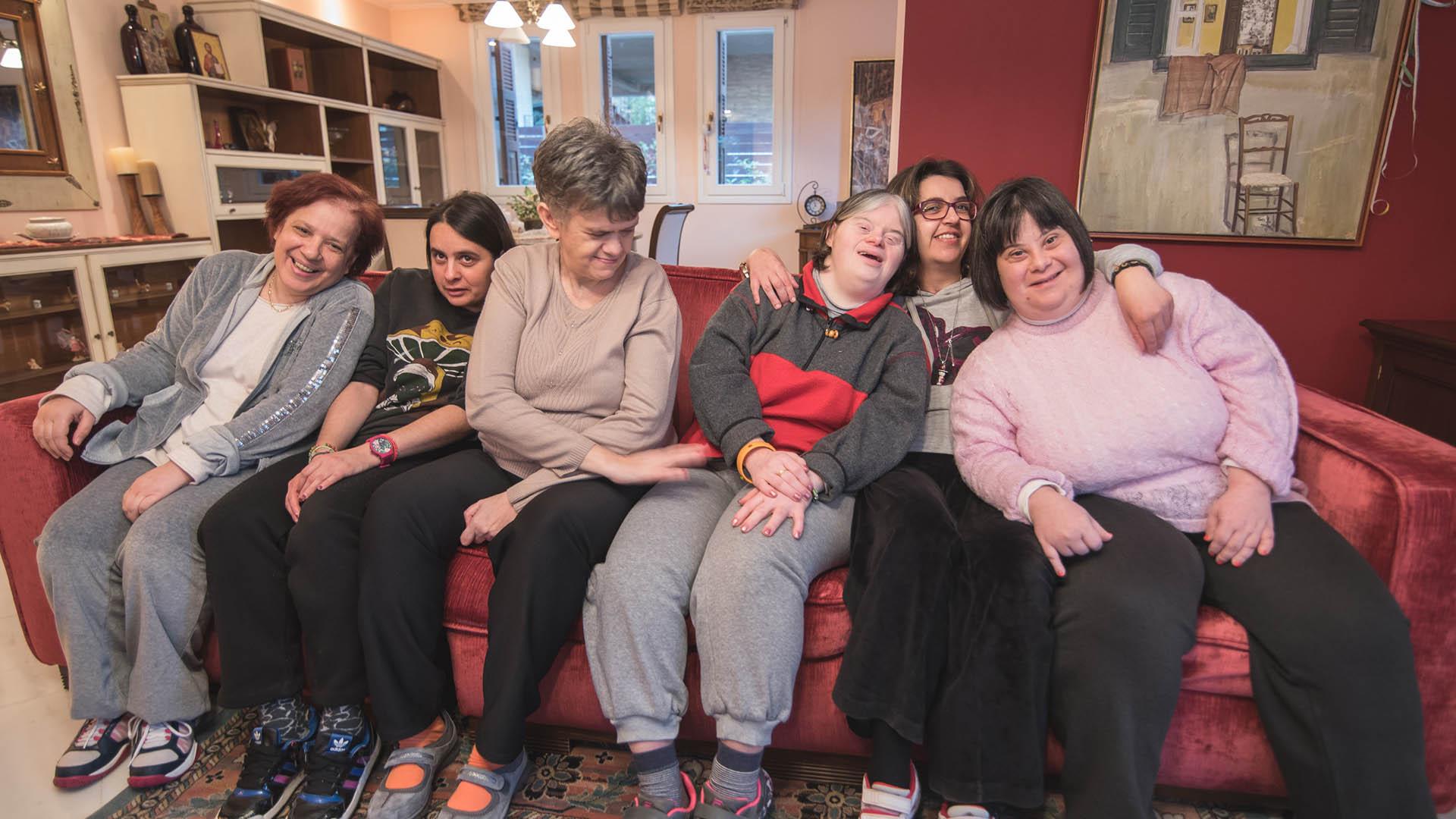 Παιδιά κάθονται με εθελόντρια στον καναπέ